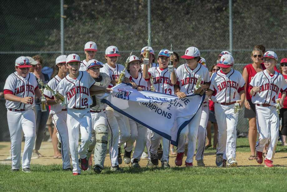 The Fairfield American team runs to the outfield with their trophies and the District 2 Championship banner after defeating the Trumbull American team in the District 2 Little League championship game played Sunday at Unity Park in Trumbull. Photo: Mark Conrad / For Hearst Connecticut Media / © 2017 Mark F Conrad