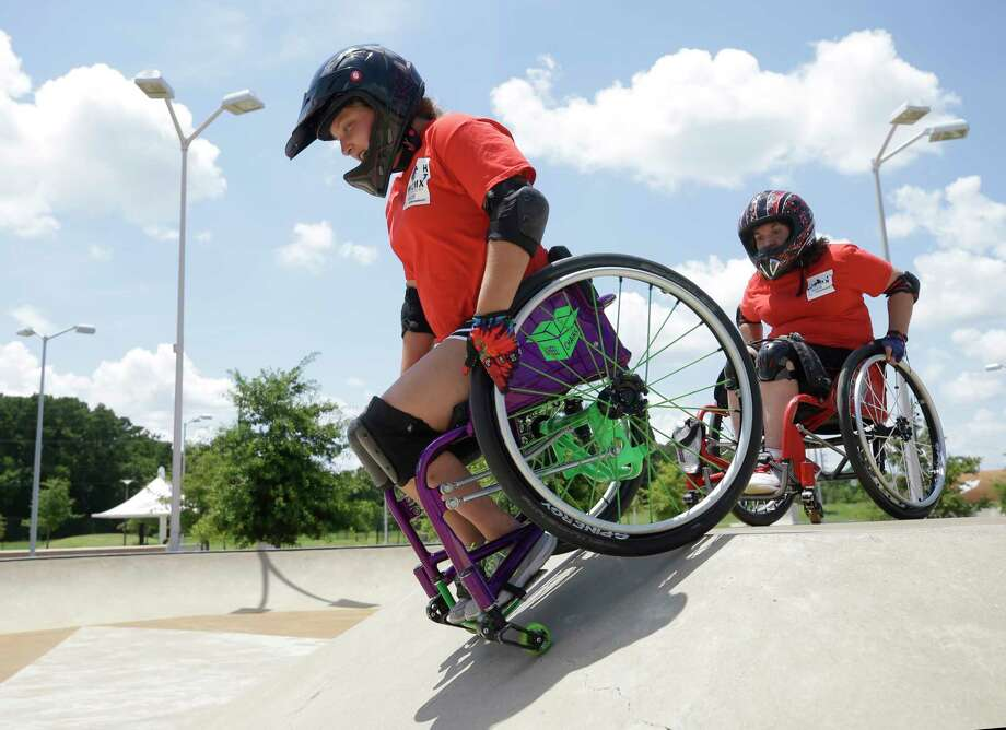 Megan Way, left, of Aledo and Gretchen Bailey, right, maneuver down a ramp during a wheelchair motocross event at North Houston Skate Park, 12351 Kuykendahl Rd., Sunday, July 16, 2017, in Houston. Photo: Melissa Phillip, Houston Chronicle / © 2017 Houston Chronicle