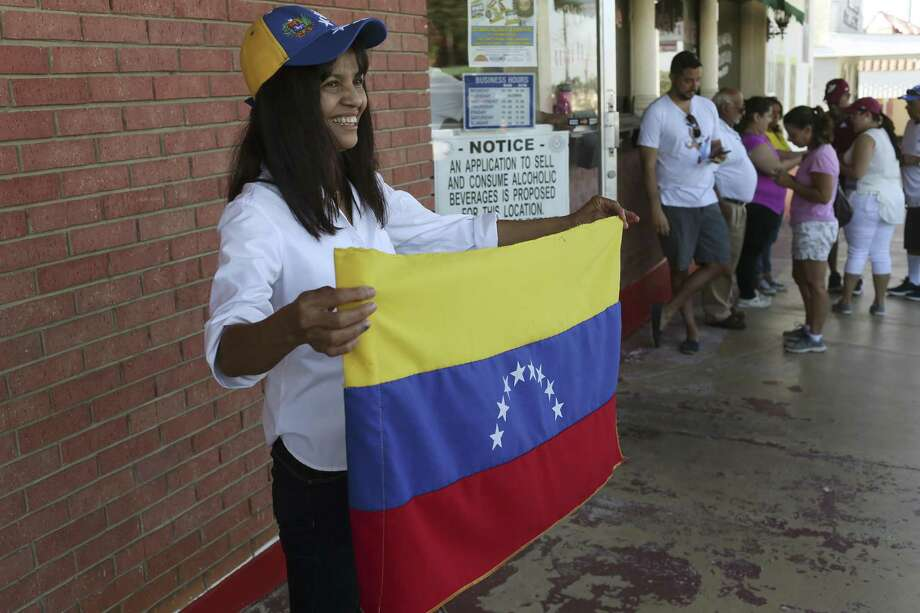 Carmen Mullagan, 55, poses with the Venezuelan flag after casting her vote in a non-binding poll at La Fonda Latina Restaurant, Sunday, July 16, 2017. The Venezuelan community is voting in 559 cities and 101 countries, including here in San Antonio, in a non-binding plebiscite against Socialist President Nicolas Maduro's plans for a new assembly. Photo: Jerry Lara /San Antonio Express-News / San Antonio Express-News