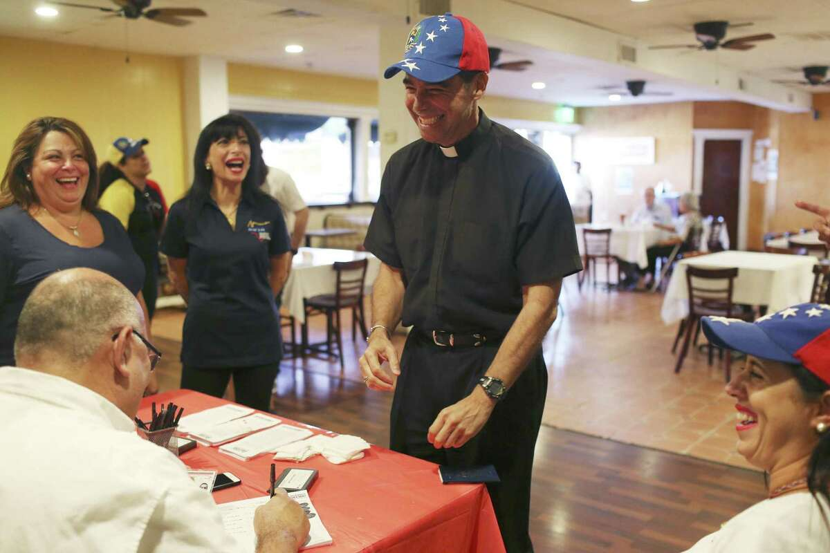 The Rev. Octavio Muguerza tries on a Venezuelan flag cap after casting his vote in a non-binding poll at La Fonda Latina Restaurant, Sunday, July 16, 2017.