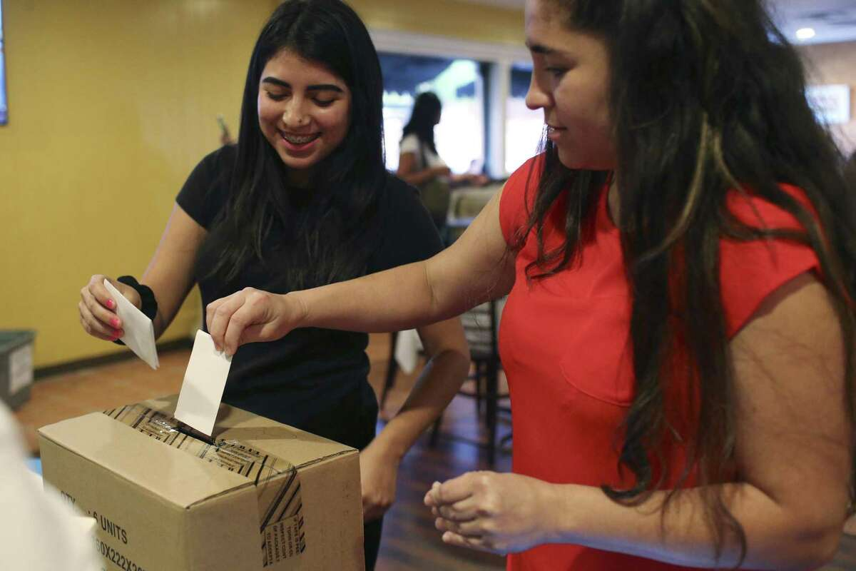 Alexandra Buada, 18, left, and her mother, Marvia Herrera, 38, cast their votes in a non-binding poll at La Fonda Latina Restaurant, Sunday, July 16, 2017.