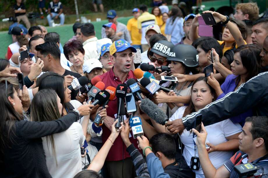 Opposition leader Henrique Capriles speaks to the press at a polling station in Caracas on July 16, 2017 during an opposition-organized vote against Venezuelan President Nicolas Maduro's plan to rewrite the constitution. Authorities have refused to greenlight the vote that has been presented as an act of civil disobedience and supporters of Maduro are boycotting it. Protests against Maduro since April 1 have brought thousands to the streets demanding elections, but has also left 95 people dead, according to an official toll. Photo: FEDERICO PARRA/AFP/Getty Images