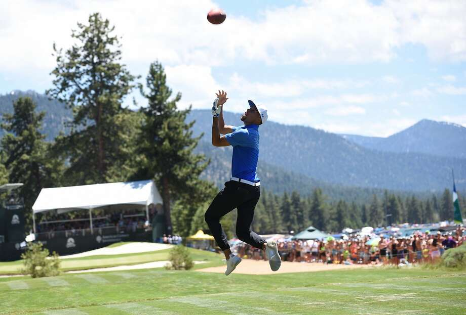 Stephen Curry catches a long pass from Tony Romo on the 17th Fairway  of the American Century Championship in Stateline Nevada on Sunday July 16, 2017. Photo: Jeff Bayer