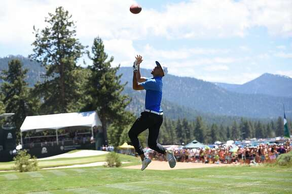 Stephen Curry catches a long pass from Tony Romo on the 17th Fairway  of the American Century Championship in Stateline Nevada on Sunday July 16, 2017.