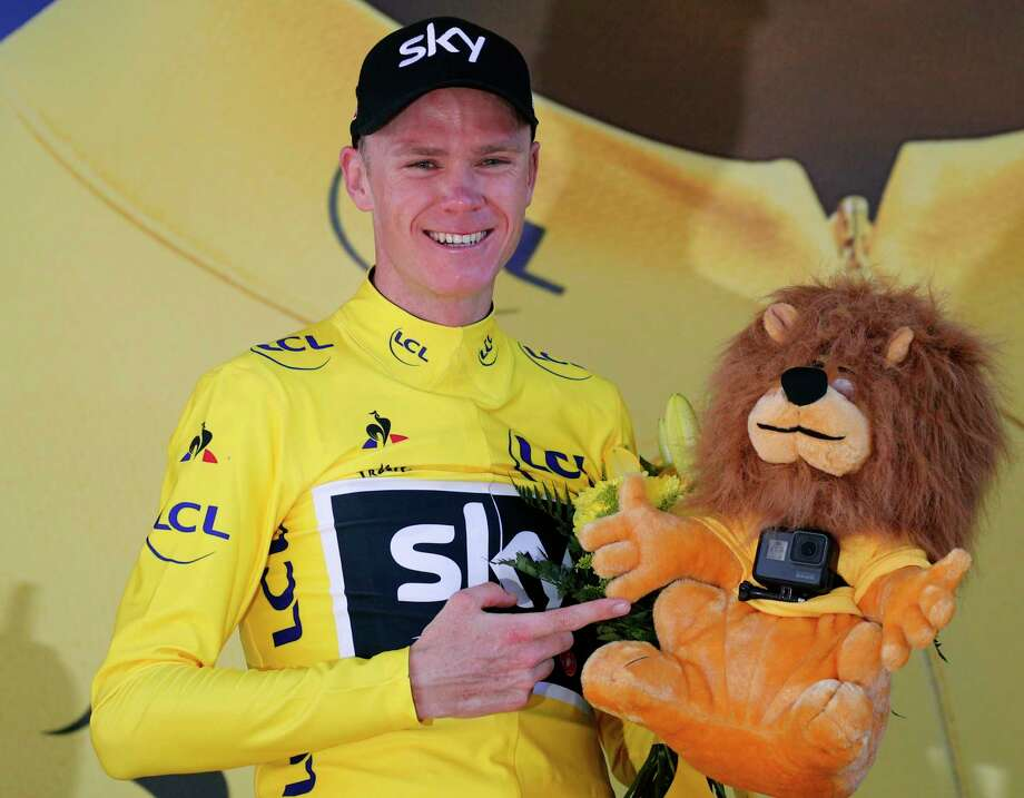 Britain's Chris Froome, wearing the overall leader's yellow jersey, points at the small camera attached to the yellow jersey's mascot on the podium of the fifteenth stage of the Tour de France cycling race over 189.5 kilometers (117.8 miles) with start in Laissac-Severac l'Eglise and finish in Le Puy-en-Velay, France, Sunday, July 16, 2017. (AP Photo/Christophe Ena) ORG XMIT: PDJ123 Photo: Christophe Ena / Copyright 2017 The Associated Press. All rights reserved.