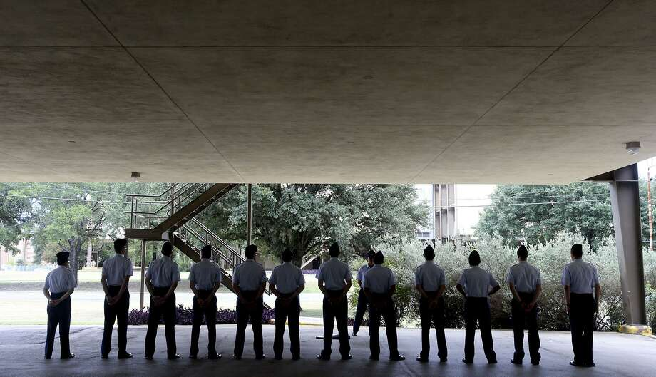 Air Force trainees line up Thursday July 13, 2017 under what is called an overhang at one of Lackland Air Force Base's older dorm buildings built in the early 1970s. The Air Force's Air Education and Training Command is mapping construction plans that is calling for modernization of key facilities such as dormitories. Photo: John Davenport /San Antonio Express-News / ©San Antonio Express-News/John Davenport