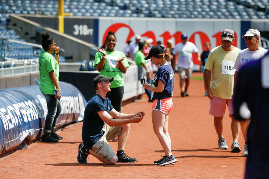Matthew Fuller pops the question to Caitlyn Henry during the Damon Runyon 5K on July 15 at Yankee Stadium. Both are from Castleton-on-Hudson. She said 'yes.' Photo: James Petrozzello / © James Petrozzello All Rights Reserved