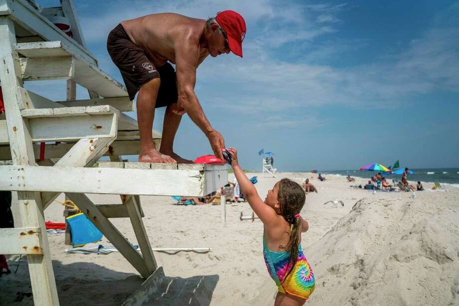 Gerry Lambert, who started as a lifeguard in 1961, takes a pair of sunglasses found in the water while working at Tobay Beach in Oyster Bay, N.Y., July 11, 2017.  At 73, Lambert is the oldest lifeguard at Tobay Beach, an oceanfront expanse on the South Shore of Long Island just east of Jones Beach. (Johnny Milano/The New York Times) ORG XMIT: XNYT23 Photo: JOHNNY MILANO / NYTNS