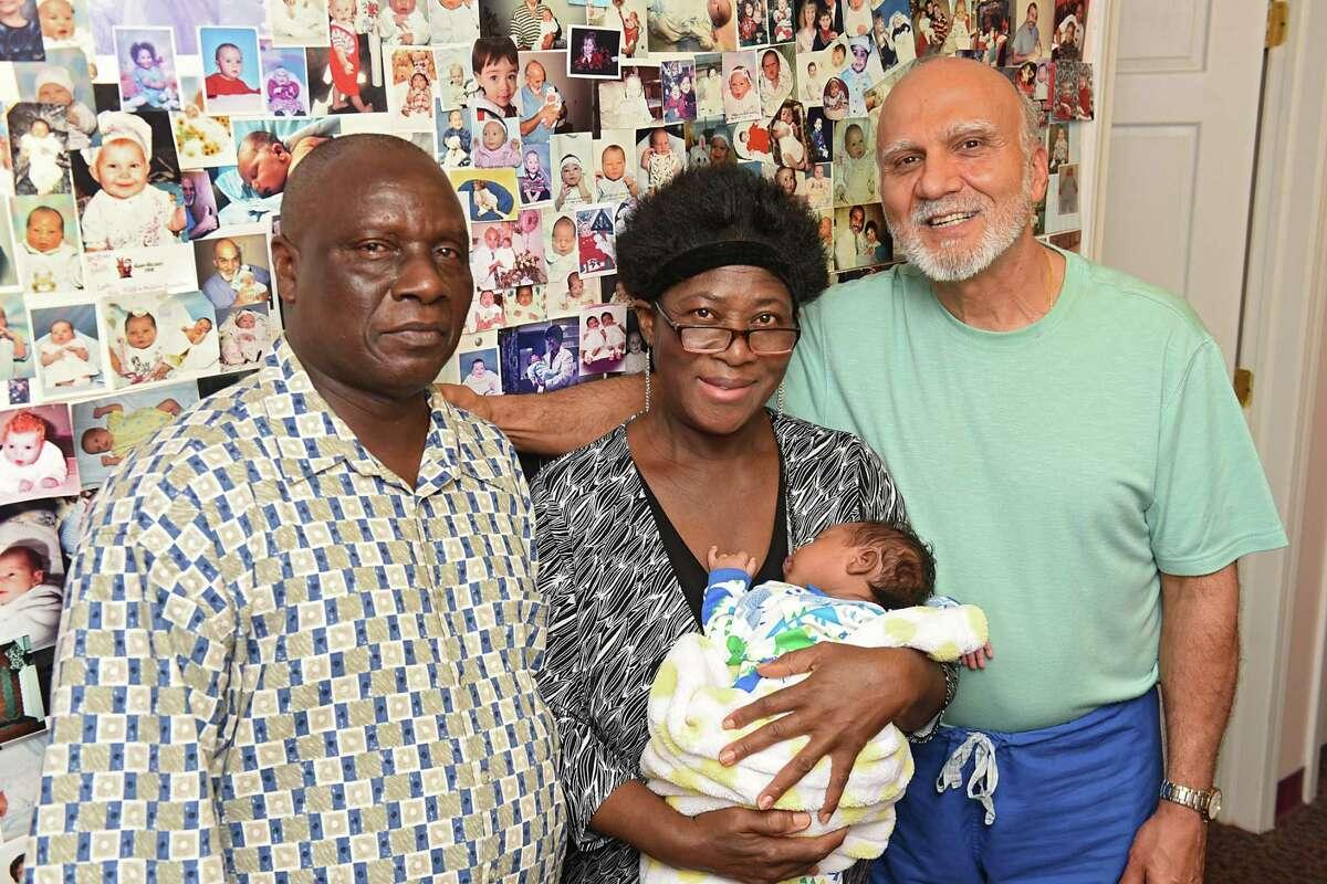 Isaiah Somuah Anim, 59, and his wife Akosua Budu Amoako, 59, pose with their son Isaiah Somuah Anim, Jr. and Dr. Khushru Irani's office on Thursday, July 13, 2017 in Niskayuna, N.Y. (Lori Van Buren / Times Union)