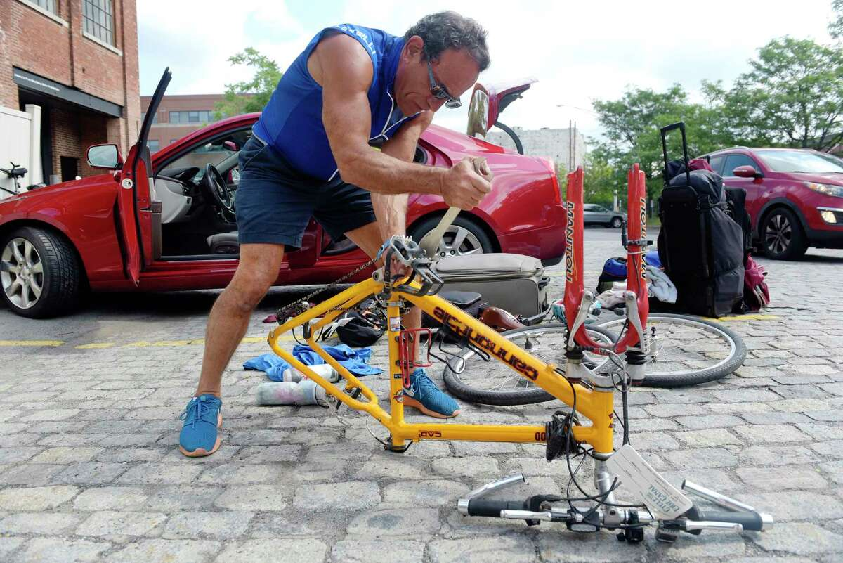 John Leccesse of Greenville, NC takes his bike apart to pack it into his car after finishing the 400-mile cross-state Cycle the Erie Canal trip on Sunday, July 16, 2017, in Albany, N.Y. Leccesse, who grew up in Queens, took part in the trip for the first time this year.