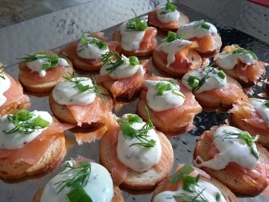 Bagel chips topped with smoked salmon, dill, crème fraîche and lemon juice can make for a serious party appetizer. Photo: Emily Spicer /San Antonio Express-News