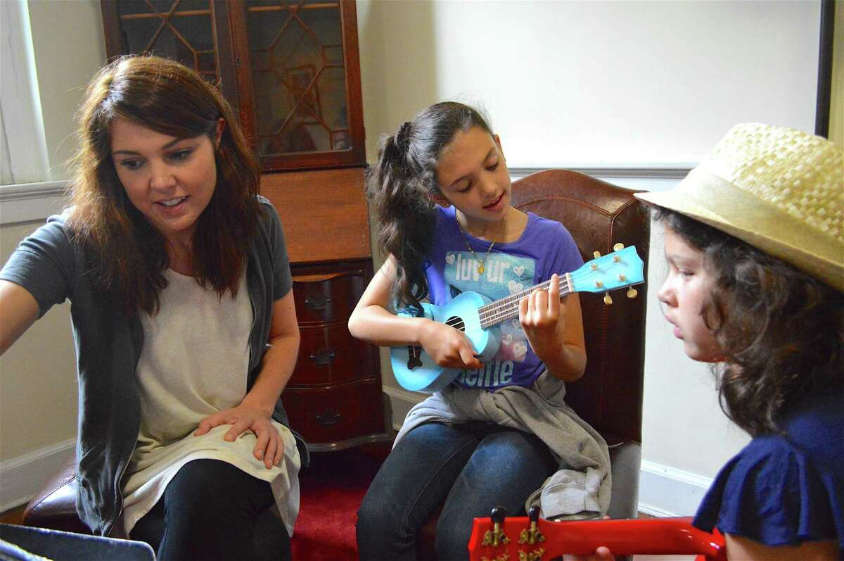 Angie Lindroth, a music teacher at Holmes Elementary School, works with Lydia Badaracco, 9, of Norwalk, center, and Eliza Sonnenblick, 10, of Darien, at the Rock Out Summer Camp, held at First Congregational Church of Darien through the Parks & Recreation Department, Friday, July 14, 2017, in Darien, Conn.
