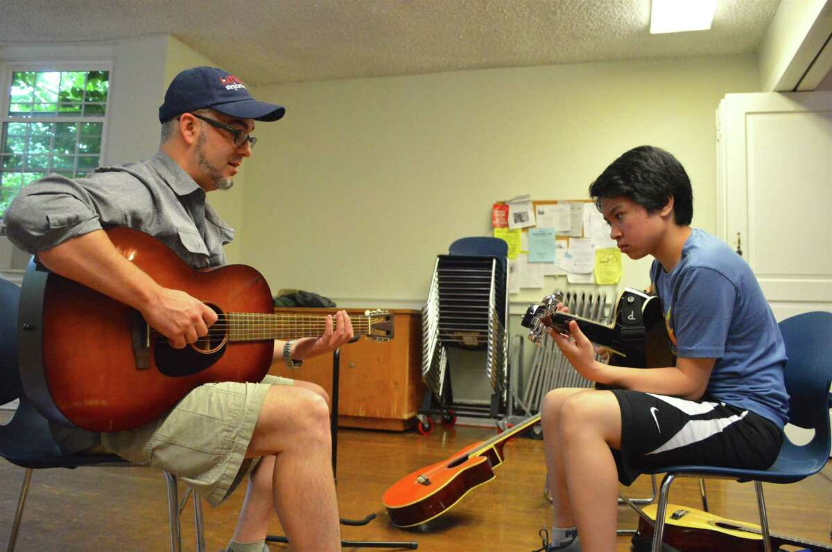 Ben Kibbey, professional musician and music teacher at Saxe Middle School in New Canaan, works with Shawn Ignacio, 14, of Norwalk, at the Rock Out Summer Camp, held at First Congregational Church of Darien through the Parks & Recreation Department, Friday, July 14, 2017, in Darien, Conn.