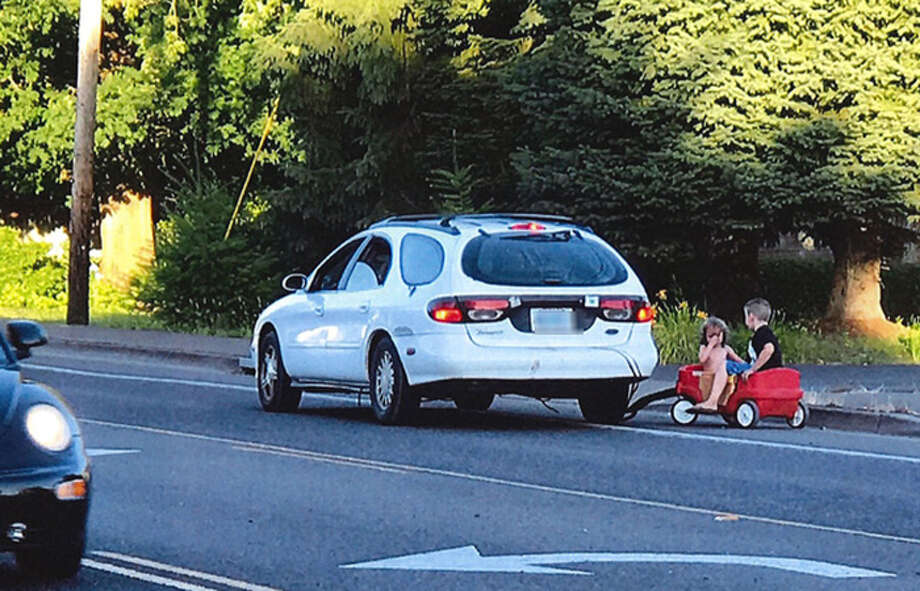 A photo taken by a witness shows two children in a red wagon after they were towed behind their mother's car, police say. (Springfield Police Department)>>Here is a list of parents who've been arrested or charged in crimes...