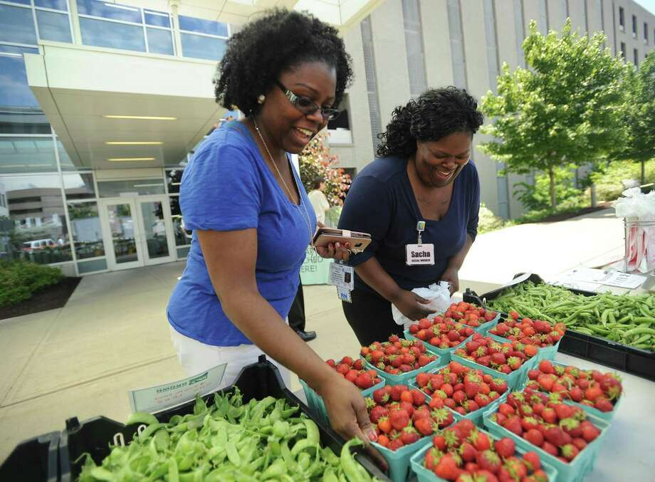 St. Vincent's Medical Center employees Porsha Sidbury, left, of West Haven, and Sacha Carswell, of Bridgeport, visit the weekly farmers market outside the hospital at 2800 Main Street in Bridgeport, Conn. The hosptail will host a cooking demo by a local chef from noon to 1 p.m. Tuesday, July 19, 2017 at the site of its farmers' market. Photo: Brian A. Pounds / Hearst Connecticut Media / Connecticut Post