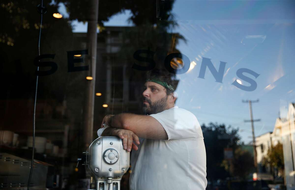 Evan Bloom, co-owner Wise Sons Jewish Delicatessen, looks out a window as staff opens the front gate for dinner at at Wise Sons Jewish Delicatessen on Thursday, October 2, 2014 in San Francisco, Calif.