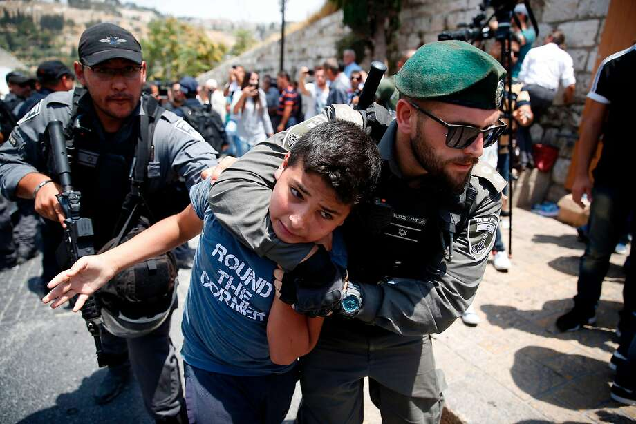 Israeli officers detain a Palestinian youth during a protest at an entrance to Al-Aqsa Mosque in Jerusalem. Photo: AHMAD GHARABLI, AFP/Getty Images