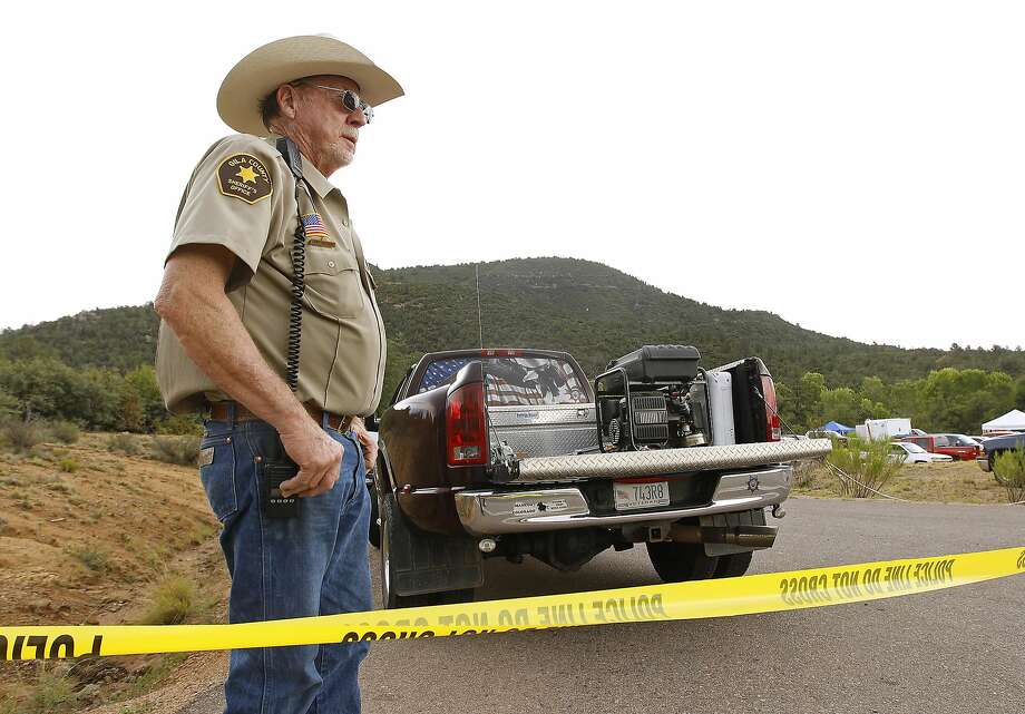 Sheriff's Deputy Larry Hassinger guards an entrance Sunday to the area near Payson, Ariz., that was hit by flooding. Photo: Ralph Freso, Associated Press