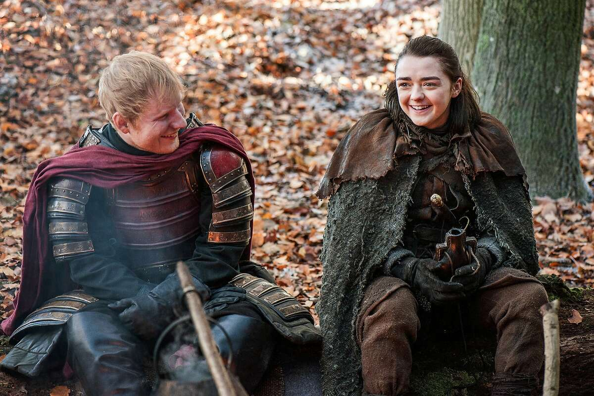 """This image released by HBO shows Ed Sheeran, left, and Maisie Williams in a scene from """"Game of Thrones."""" Sheeran appeared as a Lannister soldier leading a group in song in the season premiere of the hit HBO fantasy drama, which debuted on the premium cable channel Sunday night. (Helen Sloan/HBO via AP)"""