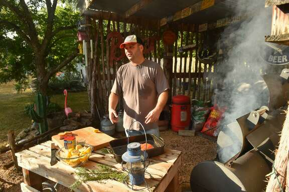 Chuck Blount prepares smoked salmon in his backyard cooking area for the Food Shack.