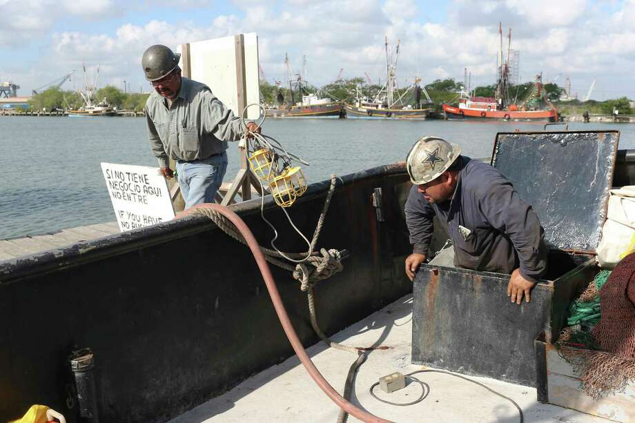 Workers check for water leaks on a shrimp trawler docked at a marina near the Port of Brownsville, Texas, Wednesday, June 21, 2017. The Brownsville-Port Isabel shrimping fleets uses up to 500 H2B visa yearly but could come up a few hundred short this year. The season is schedule to start on July 15 and the visas take about 30 days to process. Photo: JERRY LARA / © 2017 San Antonio Express-News