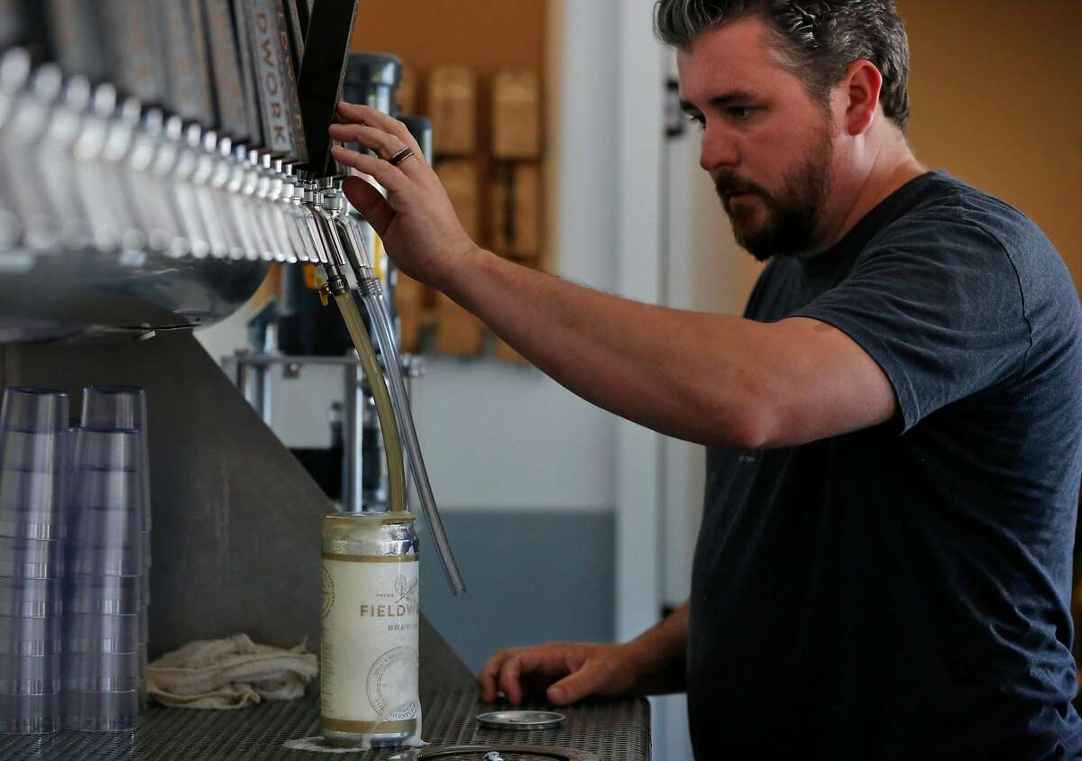 Ryan Murphy, General Manager, fills a growler with beer at Fieldwork Brewing Company July 14, 2017 in San Mateo, Calif.