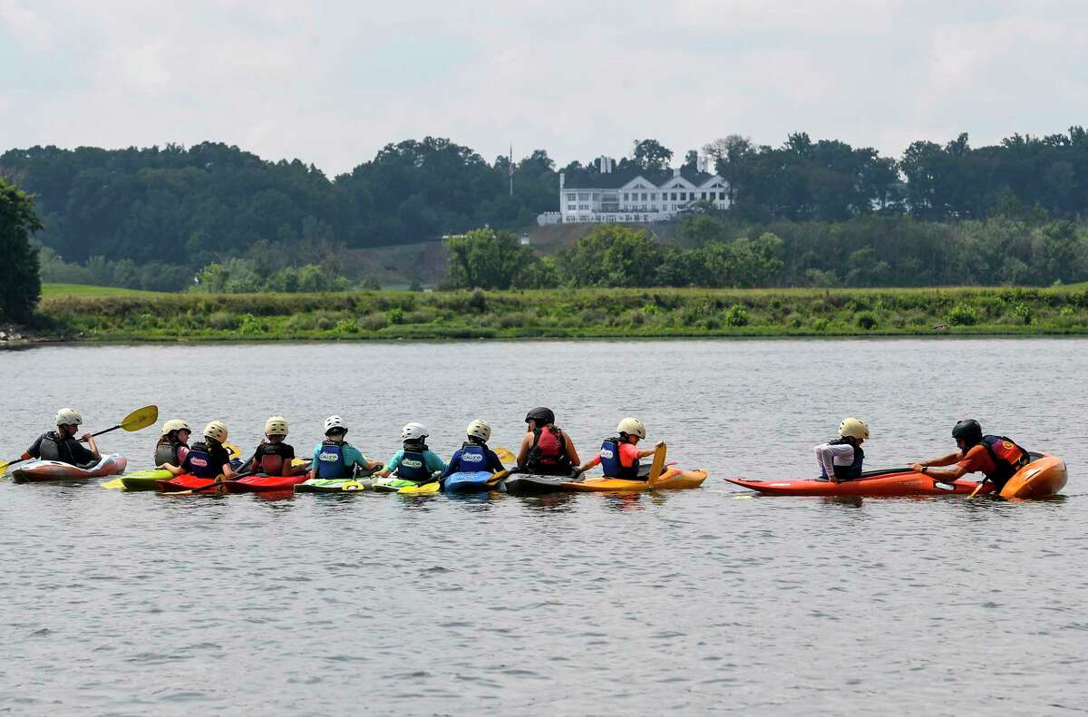 With the Trump National Golf Club clubhouse in the background, Camp Calleva kayak instructor Steve McKone helps one of his campers while teaching a lesson on the Potomac River on Monday.
