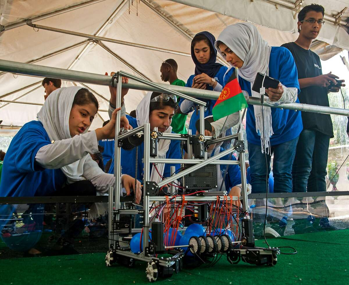 Members of the Afghani all-girls robotics team work with their robot in the practice area July 17, 2017, between 2017 FIRST Global Challenge competitions at DAR Constitution Hall, in Washington, DC. A team of Afghan girls prevailed in their first encounter at an international robotics competition in Washington Monday, but the result was perhaps less significant than the fact they made it at all. Twice denied visas into the United States until a late intervention by the Trump administration, the team of six from the war-torn country's western Herat are now determined to strike a blow for gender equality and national pride. / AFP PHOTO / PAUL J. RICHARDSPAUL J. RICHARDS/AFP/Getty Images
