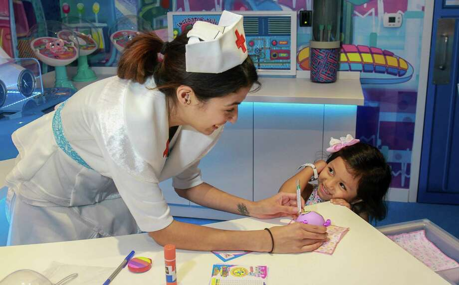 Adalyn Vargas, 3, watches nurse Natalie Martinez check her new doll during the adoption process in the new Distroller toy store in the Galleria.  (For the Chronicle/Gary Fountain, July 13, 2017) Photo: Gary Fountain, For The Chronicle / Copyright 2017 Gary Fountain