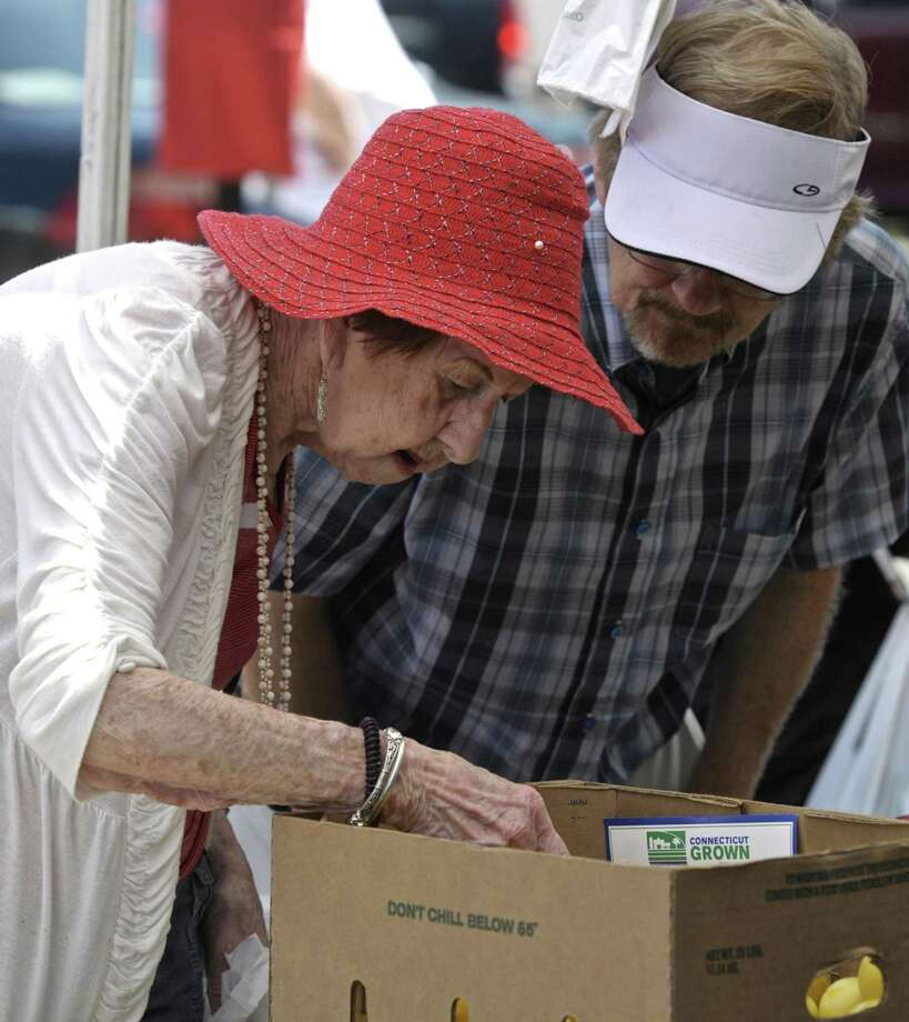 Agnes Fricker, of Danbury, looks through a box of yellow plums at the Smith's Acres booth, while Michael Andrews, of Newtown, looks on at the CityCenter Danbury Farmers Market, is held every Friday, from 11 a.m. to 5 p.m. in Kennedy Park from Mid-June through the end of September. Friday, August 14, 2015, in Danbury, Conn. Photo: H John Voorhees III / Hearst Connecticut Media / The News-Times