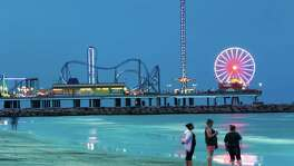 The lights of the Pleasure Pier light up the night sky over the water in Galveston.