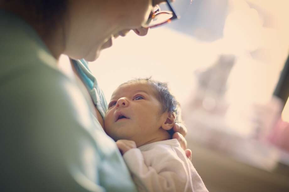 A woman holding a newborn baby is shown in this getty stock photo infant mortality