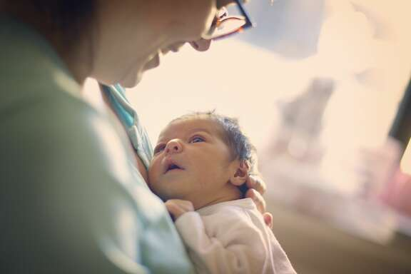 A woman holding a newborn baby is shown in this Getty stock photo.