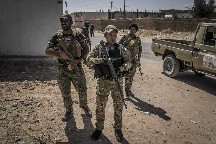 Shiite militiamen patrol last month in al-Mazraa, Iraq. Iran, a Shiite state, has been trying to use Iraq to effectively control a corridor from Tehran to the Mediterranean.