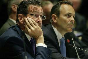 """Connecticut Democratic Gov. Dannel Malloy, left, and Kentucky Republican Gov. Matthew Bevin listens to a presentation during a session called """"Curbing The Opioid Epidemic"""" on the first day of the National Governor's Association meeting in Providence, R.I. on Thursday."""