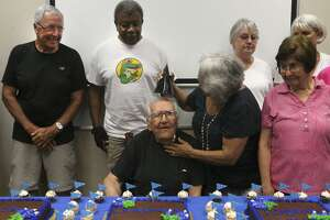Elaine Odell (second from right, foreground) places a party hat on the head of Charles Joesph Kunetka (center) during the celebration of Kunetka's 107th birthday at HealthLink Fitness and Wellness Center. Prior to the party, Kunetka enjoyed his weekly exercise session with some of his friends who also attended the party.