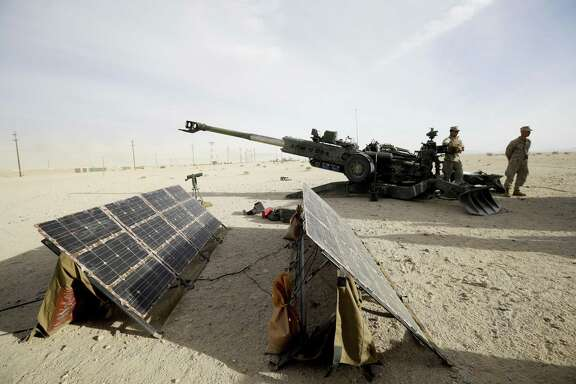 In this Dec. 7, 2016 photo, Marines stand near an artillery piece that links to solar panels during an exhibition of green energy technology in Twentynine Palms, Calif. The Marine Corps and Navy have led an unprecedented push to ease the Department of Defense's reliance on fossil fuels under the Obama administration. Those projects championed under Obama now face uncertainty under President-elect Donald Trump, who has chosen a Cabinet with climate change skeptics and fossil fuel promoters. (AP Photo/Gregory Bull)