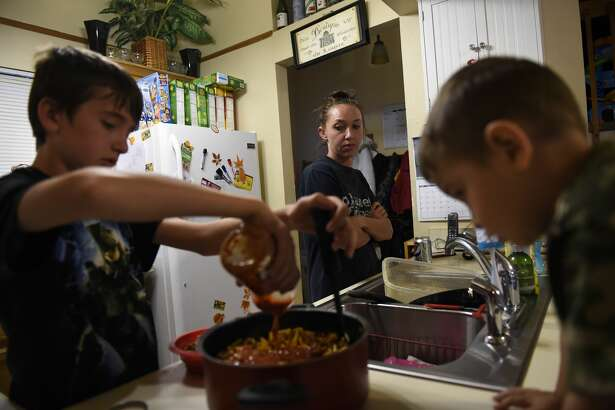 LAFAYETTE, CO. - April 14, 2015: Thirteen year old Ellijah Weber putting the finishing touches on his macaroni, cheese, beef and salsa dinner as his mom Brittany Weber and younger brother Elliah Weber-Villela two years old, watch at their home in Lafayette. April 14, 2015 Lafayette, CO (Photo By Joe Amon/The Denver Post via Getty Images)