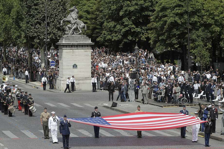 U.S soldiers display a huge American flag during the Bastille Day parade in Paris, Friday, July 14, 2017. Paris has tightened security before its annual Bastille Day parade, which this year is being opened by American troops with President Donald Trump as the guest of honor to commemorate the 100th anniversary of the United States' entry into World War I. (AP/Photo/Markus Schreiber) Photo: Markus Schreiber, Associated Press