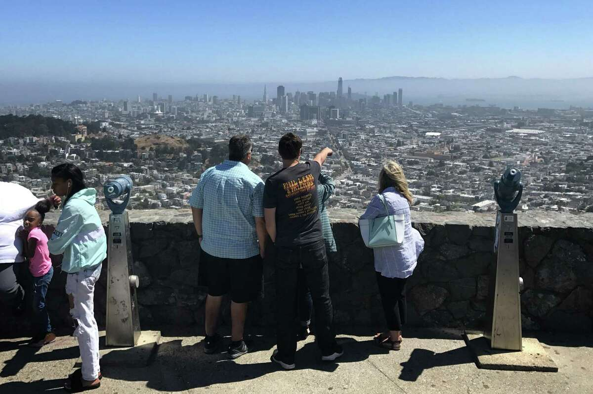 Visitors look out over San Francisco from Twin Peaks the day after 71-year-old Edward French was shot and killed in the parking lot.