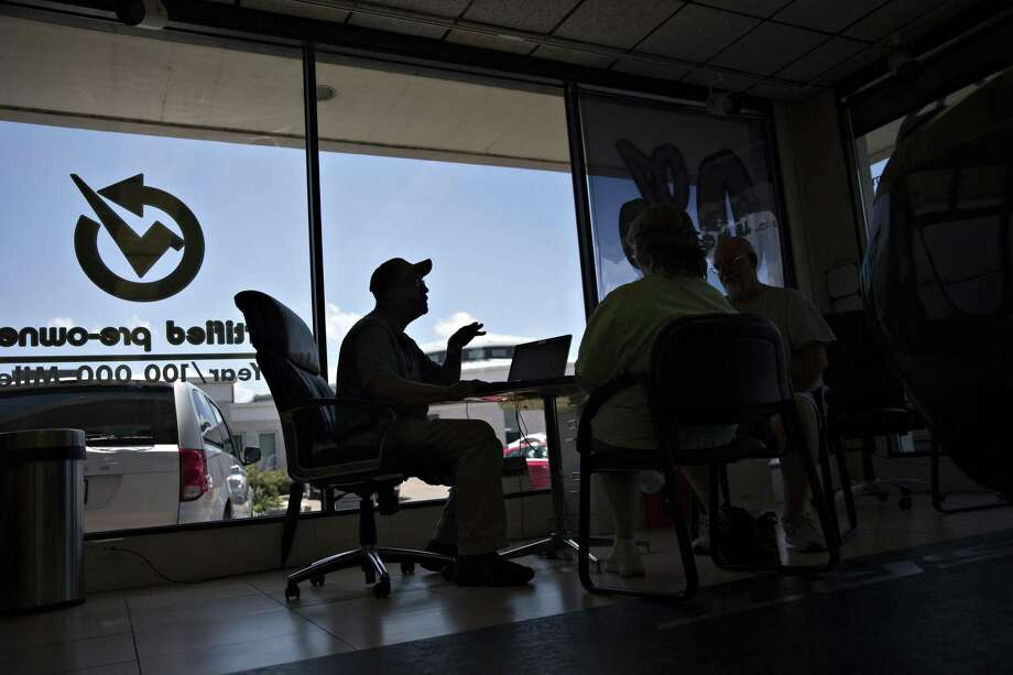"""A salesman in Moline, Ill., works with a customer in the showroom of a Fiat Chrysler dealership. After its 2009 bankruptcy, Chrysler sought a dedicated lender to help customers finance their cars quickly. It found Santander and its expertise in """"automated decisioning."""" Photo: Daniel Acker /Bloomberg / © 2017 Bloomberg Finance LP"""