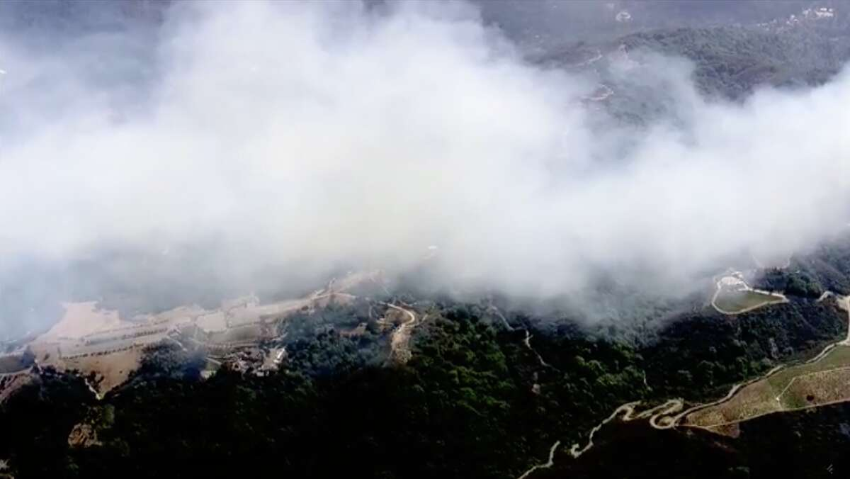 A wildfire burned through vegetation in Saratoga Monday afternoon, sending a dense cloud of smoke over the city.