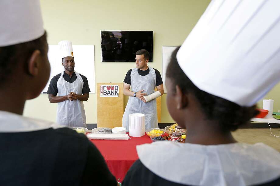 San Antonio FC forward AJ Ajeakwa (left) and goalkeeper Diego Restrepo talk with children part of the Refugee School Impact Program with Catholic Charities of San Antonio during a cooking class held Monday July 17, 2017 at the San Antonio Food Bank. Photo: Edward A. Ornelas, Staff / San Antonio Express-News / © 2017 San Antonio Express-News