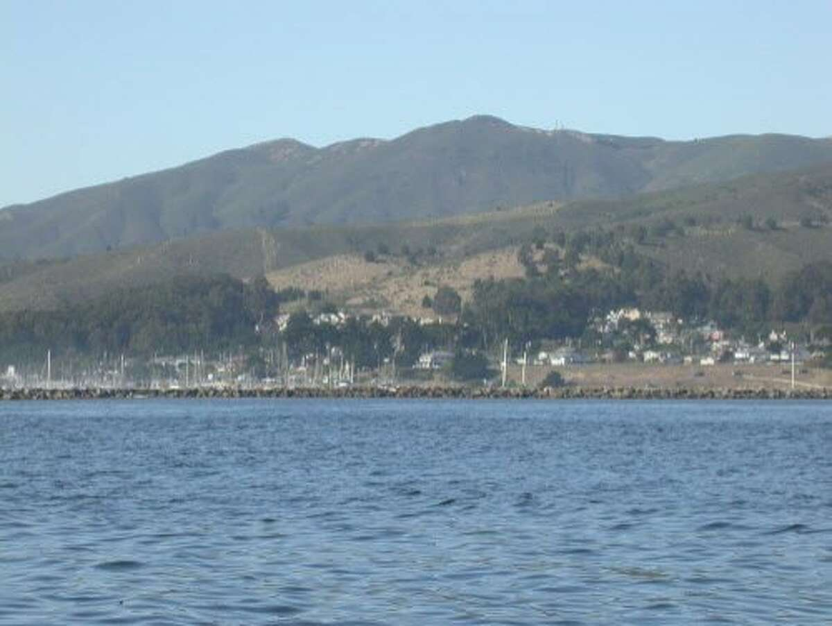 Montara Mountain looms above the San Mateo County coast, rising up between Montara and Pacifica, and seen here from a boat just offshore Pillar Point Harbor