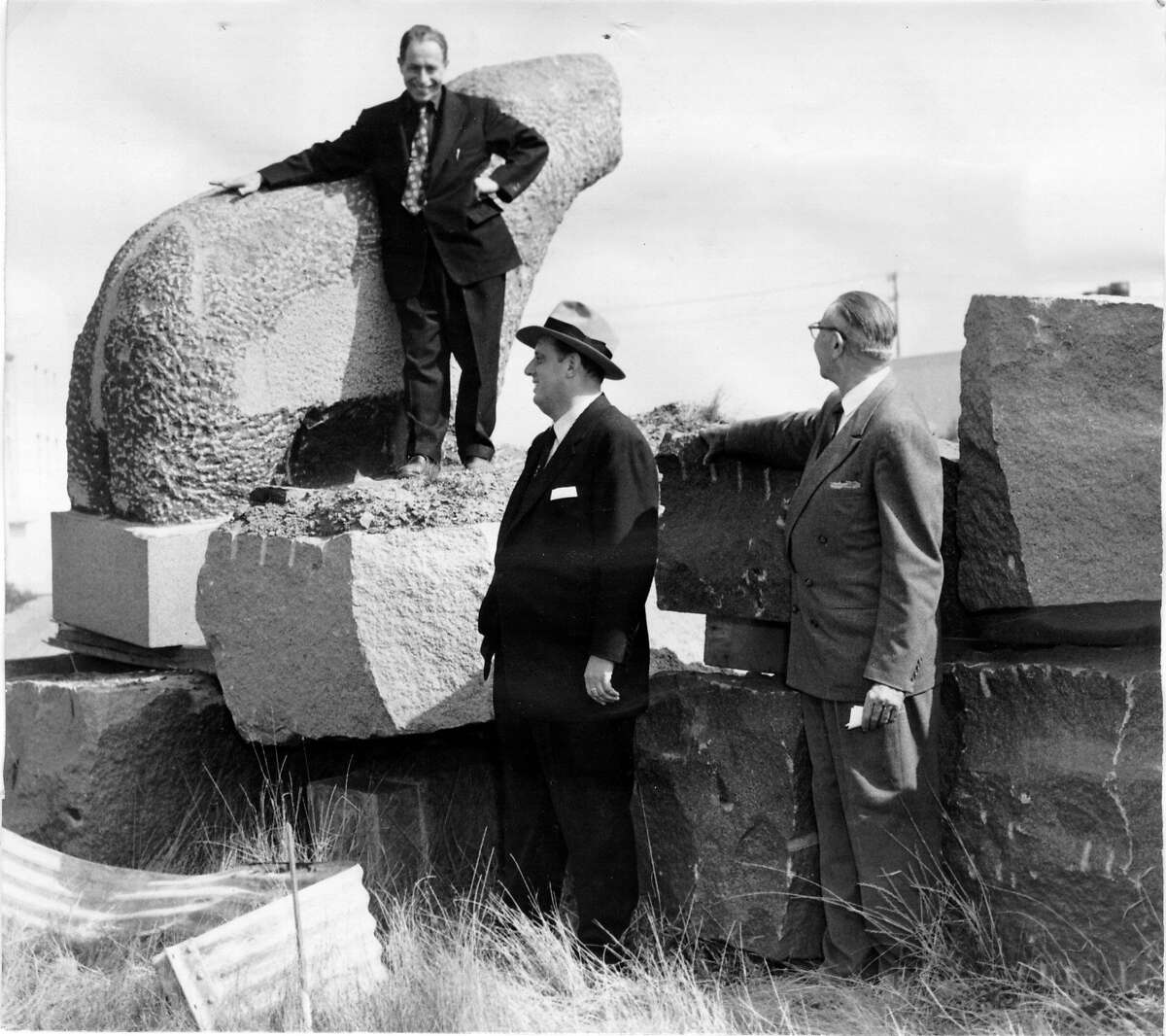 Beniamino Bufano posed atop one of his bear sculptures in 1956.
