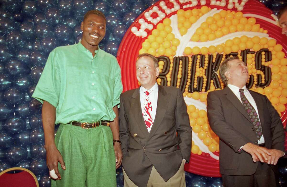 07/30/1993 - Houston Rockets center Hakeem with new Rockets owner Leslie Alexander at press conference announcing completion of the sale. Previous Rockets owner Charlie Thomas is at right.