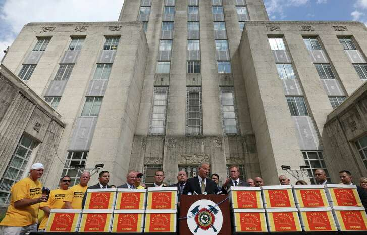 Former City Attorney David Feldman, center, talks to media about the more than 32,000 signatures Houston firefighters collected in an effort to put equal pay on the ballot during a press conference outside City Hall on Monday.