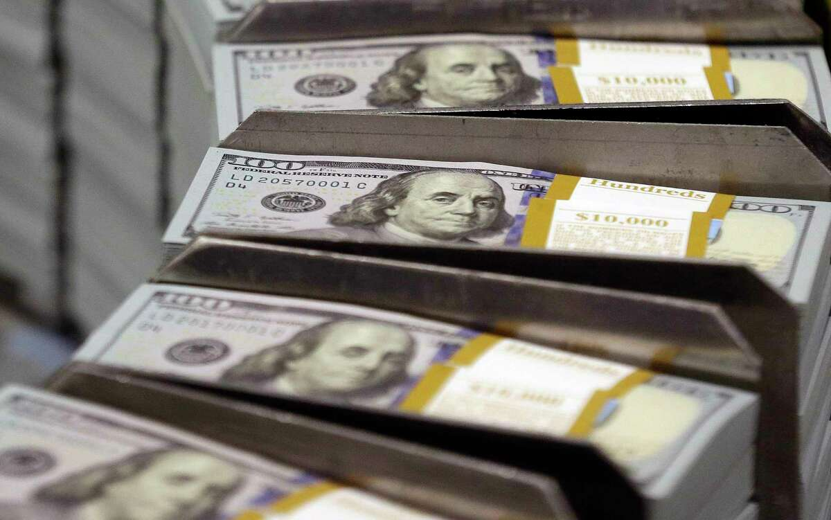 Freshly cut stacks of $100 bills make their way down the line at the Bureau of Engraving and Printing Western Currency Facility in Fort Worth. Credit card companies are trying to persuade merchants to go cashless.