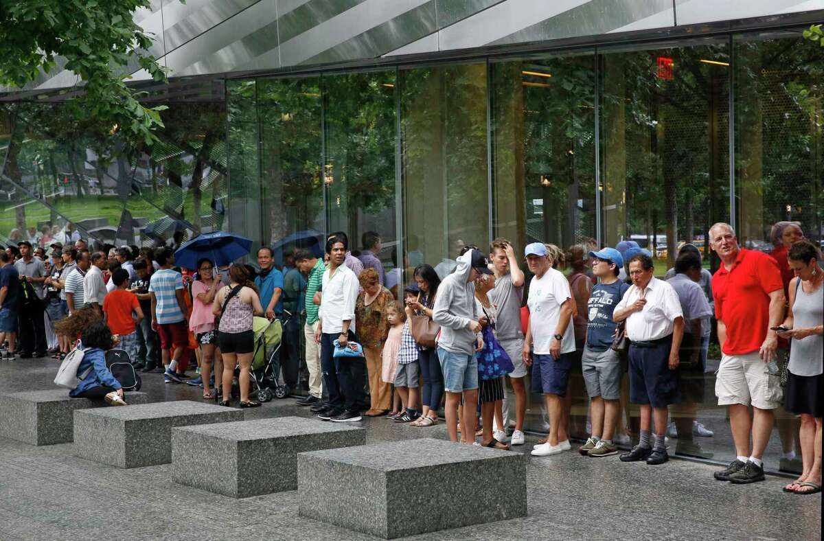 """In this July 11, 2017 photo, visitors to the National September 11 Memorial and Museum take shelter beneath a museum overhang during a sudden rainstorm in New York. Last winter the U.S. tourism industry worried about a """"Trump slump,"""" fearing that Trump administration policies might discourage international travelers from visiting the U.S. But statistics from the first half of 2017 suggest that the travel to the U.S. is robust and a number of sectors have reported increased international visitation, with one expert calling it a """"Trump bump."""" The museum is among those reporting more international visitors this year compared to the same period in 2016. (AP Photo/Kathy Willens)"""