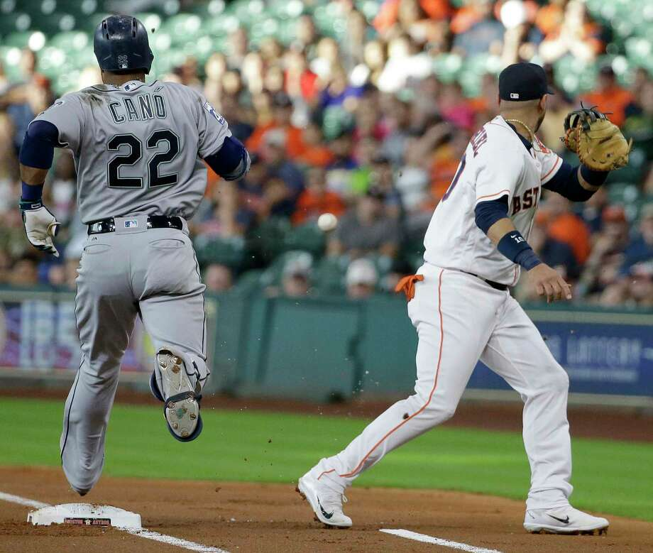 Houston Astros Yuli Gurriel watches ball as Seattle Mariners Robinson Cano reaches first base on a throwing error by pitcher Lance McCullers Jr. during the  first inning at Minute Maid Park Monday, July 17, 2017, in Houston. Photo: Melissa Phillip, Houston Chronicle / © 2017 Houston Chronicle